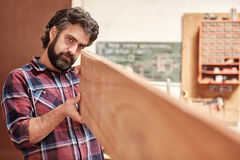 Craftsman in his workshop looking down length of wooden plank Royalty Free Stock Photography