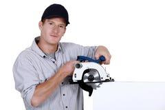 Craftsman holding an electric saw Stock Photos