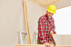 Craftsman holding saw and cutting wood. At construction site Royalty Free Stock Images