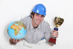Craftsman holding trophy and globe Stock Images
