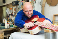 Craftsman holding unfinished guitar Royalty Free Stock Photo