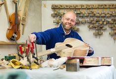 Craftsman holding unfinished guitar Royalty Free Stock Photography