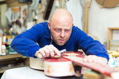 Craftsman holding unfinished guitar Royalty Free Stock Images