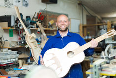 Craftsman holding unfinished guitar Royalty Free Stock Photos