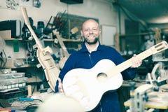 Craftsman holding unfinished guitar Stock Image