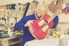 Craftsman holding unfinished guitar Royalty Free Stock Photos