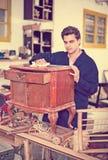 Craftsman inspecting nightstand before restoration Stock Photo