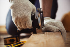 Craftsman with instruments. Close-up of craftsman hands working with construction instruments on the floor in his workshop Stock Photography