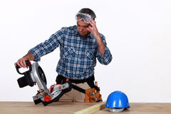 Craftsman looking at electric saw Royalty Free Stock Photo
