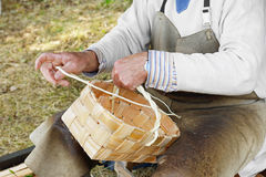 Craftsman making baskets. Basket weaving, basketry, or basket making is the process of weaving pliable materials into a basket or other similar form. People and stock photo