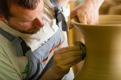 Craftsman making huge vase from fresh wet clay on pottery wheel Stock Photo