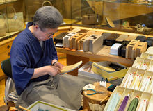 Craftsman making sandals, Kyoto, Japan royalty free stock photo