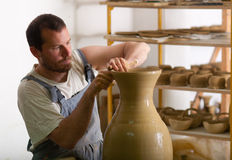 Craftsman making vase from fresh wet clay Stock Photos