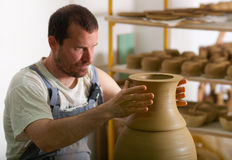 Craftsman making vase from fresh wet clay Stock Photo