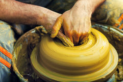 Craftsman making vase from fresh wet clay Stock Images