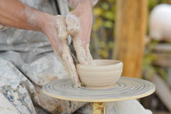 Craftsman making vase from fresh wet clay on pottery wheel Stock Photos