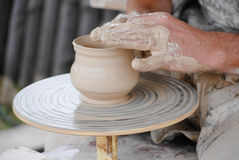 Craftsman making vase from fresh wet clay on pottery wheel stock photo