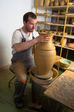 Craftsman making vase from wet clay on pottery whe. Craftsman making vase from fresh wet clay on pottery wheel Stock Image