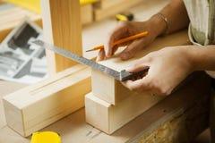 Craftsman measure wooden planks with help of ruler. Woodworker workshop Stock Image