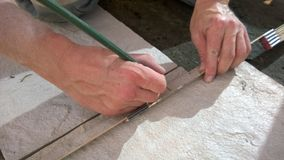 Craftsman measuring out tiles with a measuring tape and a pencil royalty free stock photography