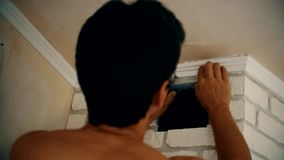 Craftsman mounting a polyurethane ceiling molding stock video