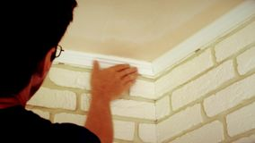Craftsman mounting a white ceiling molding stock footage