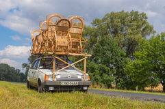 Craftsman with own wicker-work on a roof of  small car doing short stop on a roadside Royalty Free Stock Images