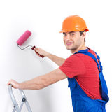 Craftsman painter stands on the stairs with roller Royalty Free Stock Photography