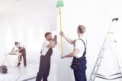 Craftsman painting white wall green while finishing interior. Wirh his crew royalty free stock photography