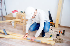 Craftsman with a pencil. Craftsman measuring wooden plank with ruler and pencil stock photography