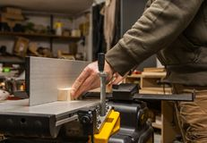 Craftsman planing wood on a jointer. stock photos