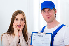 Craftsman or plumber giving overpriced invoice Royalty Free Stock Images