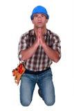 Craftsman praying. His gets a job Stock Images