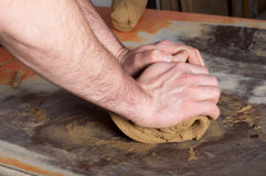 Craftsman preparing clay. In the pottery workshop by squeezing air out of it Stock Photo