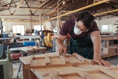 Craftsman in protective workwear sanding wood in his workshop Stock Photos