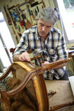 Craftsman repairing armchair Royalty Free Stock Photo
