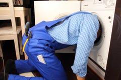 Craftsman repairing washing machine Royalty Free Stock Photography