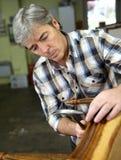 Craftsman repairing wooden armchair Stock Photography