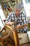 Craftsman repairing wooden chair Stock Photos