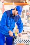 Craftsman rivet metal in workshop. Craftsman rivet metal with air compressed pistol in workshop Stock Photo