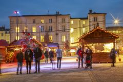 Craftsman`s cottages with illuminations of Christmas and people around on the main square of d Royalty Free Stock Photography