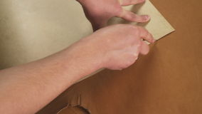 Craftsman`s hands working with a piece of leather on the table. stock video footage