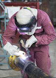Craftsman in a safety suit is welding a metal pipe Stock Photos