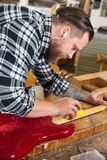 Craftsman sanding a guitar neck in wood at workshop Royalty Free Stock Images