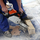 Craftsman sawing a beam with electric saw Royalty Free Stock Photos