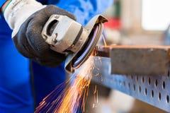 Craftsman sawing with disk grinder. Craftsman sawing metal with disk grinder in workshop Stock Photography