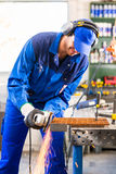 Craftsman sawing with disk grinder Royalty Free Stock Image