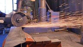 Craftsman sawing metal with disk grinder in workshop. Metal sawing close up. Worker in production sawing metal stock video footage