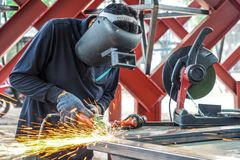 Craftsman sawing metal sparkles all around workshop. Working at noon.  stock photo