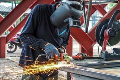 Craftsman sawing metal sparkles all around workshop. Working at noon.  royalty free stock photos